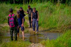 CHITWAN,尼泊尔- 2017年11月03日:横渡没有鞋子一条小河的有些游人在Chitwan国家公园 免版税库存图片