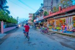 CHITWAN,尼泊尔- 2017年11月03日:骑自行车接近一个市场的未认出的人民在接近Chitwan国民的一个村庄 库存照片