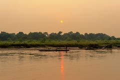 CHITWAN,尼泊尔- 2013年10月27日:驾驶在狂放的河剧烈的日落的船夫划艇在Chitwan国家公园尼泊尔 Chitw 免版税库存照片