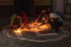 CHITWAN, NÉPAL - 27 OCTOBRE 2014 : Bougies de foudre de personnes sur la tradition de bouddhiste de symbole de svastika Le symbol Photo libre de droits