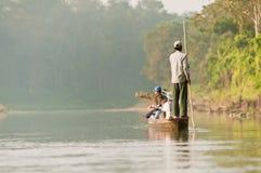 CHITWAN, NEPAL - 28 DE OUTUBRO DE 2013: Os turistas estão viajando pelo barco a remos no rio selvagem no parque nacional Nepal de Fotografia de Stock Royalty Free