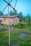CHITWAN NEPAL, LISTOPAD, - 03, 2017: Niezidentyfikowani dzieci bawić się blisko drewniani domy budowali w Chitwan, Nepal Zdjęcie Stock