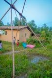CHITWAN NEPAL, LISTOPAD, - 03, 2017: Niezidentyfikowani dzieci bawić się blisko drewniani domy budowali w Chitwan, Nepal Fotografia Royalty Free