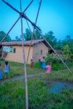 CHITWAN NEPAL, LISTOPAD, - 03, 2017: Niezidentyfikowani dzieci bawić się blisko drewniani domy budowali w Chitwan, Nepal Obrazy Stock