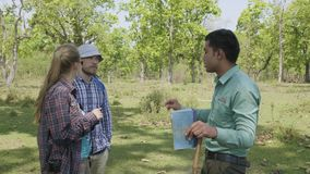CHITWAN, NEPAL - MARCH, 2018: Nepalese guide talks to european tourists about jungle flora and fauna. CHITWAN, NEPAL - MARCH, 2018: Nepalese guide talks to stock video