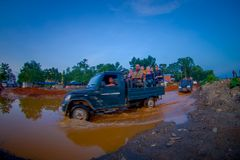 CHITWAN NEPAL - NOVEMBER 03, 2017: Oidentifierat folk som reser i den tillbaka delen av en bil som korsar en gata med Royaltyfri Foto