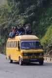CHITWAN, NEPAL - OKTOBER 26, 2013: De mensen reizen door Lokale bus, is het normaal om mensen te zien zittend op het dak van de b Royalty-vrije Stock Foto's
