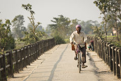 CHITWAN PARK, NEPAL - NOVEMBER 22: Unkown man on a bicycle in Ch Royalty Free Stock Images
