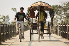 CHITWAN PARK, NEPAL - NOVEMBER 22: Unkown men on a bicycle and a Royalty Free Stock Photography