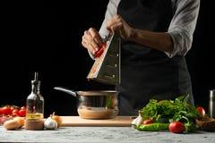 Chiuda il chef& x27; mani di s, preparanti una salsa al pomodoro italiana per i maccheroni Pizza Il concetto della ricetta di cot immagini stock libere da diritti
