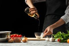 Chiuda il chef& x27; mani di s, preparanti una salsa al pomodoro italiana per i maccheroni Pizza Il concetto della ricetta di cot fotografie stock