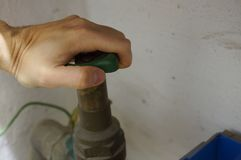 Chiuda il rubinetto - mani sulla ruota Fotografia Stock