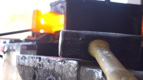 Chiuda 4k sul colpo, l'area di lavoro del fabbro, metallo fuso del ferro di pezzo fucinato con il martello stock footage