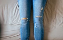 Chiuda pigro su delle gambe della donna con le blue jeans, i piedi e l'allungamento sul letto Immagine Stock Libera da Diritti