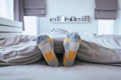 Chiuda pigro su di a piedi nudi con calzature, i piedi e l'allungamento sul letto Fotografia Stock Libera da Diritti