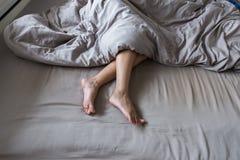 Chiuda pigro su di a piedi nudi, piedi ed allungamento sul letto Fotografia Stock Libera da Diritti