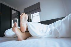 Chiuda pigro su di a piedi nudi, piedi ed allungamento sul letto Fotografia Stock