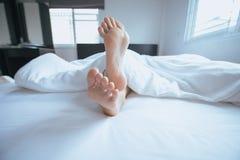 Chiuda pigro su di a piedi nudi, piedi ed allungamento sul letto Immagini Stock Libere da Diritti