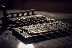 chiuda su alle corde ed al ponte della chitarra fotografia stock