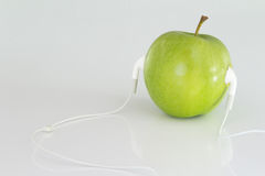 Chiuda su Apple verde concettuale con la cuffia avricolare Fotografia Stock Libera da Diritti