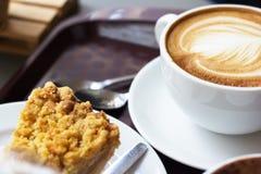 Chiuda su arte calda o sulla moca del latte del caffè in tazza bianca con la torta di mele sulla tavola di legno in caffetteria c Immagini Stock