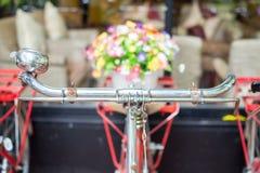 Chiuda su attuale del fuoco selettivo della mano e dei fiori della bicicletta filtrato Fotografia Stock