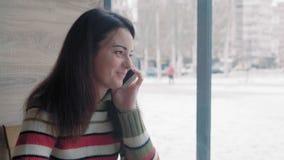 Chiuda - su, bella donna che parlano sul telefono che si siede in un caffè dell'inverno e sorridere stock footage
