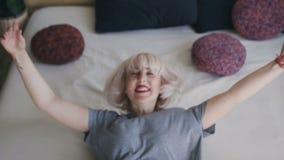Chiuda su, belle bugie bionde di divertimento nel grande letto e la rompe armi Donna sorridente in un letto bianco contro il conc archivi video