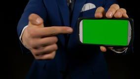 Chiuda su con la mano dell'uomo che vi invita ad esaminare lo smartphone con lo schermo verde archivi video
