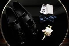 Chiuda su degli accessori dell'uomo moderno Cravatta a farfalla blu, scarpe nere, boutonniere e gemelli Immagini Stock