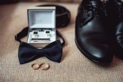 Chiuda su degli accessori dell'uomo moderno fedi nuziali, cravatta a farfalla nera, scarpe di cuoio, cinghia e gemelli Fotografie Stock