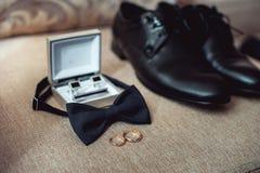 Chiuda su degli accessori dell'uomo moderno fedi nuziali, cravatta a farfalla nera, scarpe di cuoio, cinghia e gemelli Fotografie Stock Libere da Diritti