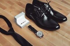 Chiuda su degli accessori moderni dello sposo fedi nuziali, cravatta nera, scarpe di cuoio ed orologio Immagine Stock