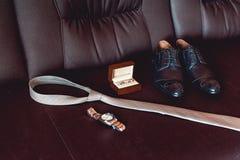 Chiuda su degli accessori moderni dello sposo fedi nuziali in una scatola di legno marrone, in una cravatta, nelle scarpe di cuoi Immagine Stock