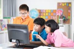 Chiuda su degli allievi asiatici sorridenti che per mezzo di un desktop computer Immagini Stock Libere da Diritti