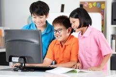 Chiuda su degli allievi asiatici sorridenti che per mezzo di un desktop computer Fotografia Stock