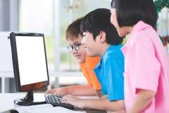 Chiuda su degli allievi asiatici sorridenti che per mezzo di un desktop computer Immagine Stock