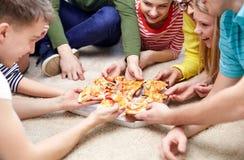 Chiuda su degli amici felici che mangiano la pizza a casa Fotografia Stock