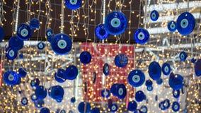 Chiuda su degli amuleti a forma di occhio blu chiamati malocchio o Nazar Appeso sul tetto Ha offuscato la bandiera turca ed ha co immagine stock libera da diritti