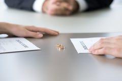 Chiuda su degli anelli e del decreto di divorzio che si trova sulla tavola immagine stock