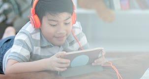 Chiuda su degli anni dell'adolescenza dell'asiatico pre riposano sul pavimento e sul gioco del computer della compressa stock footage