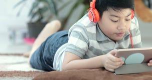 Chiuda su degli anni dell'adolescenza dell'asiatico pre riposano sul pavimento e sul gioco del computer della compressa archivi video