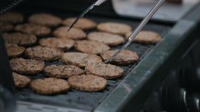 Chiuda su degli hamburger che friggono su una griglia Cuoco unico che cucina lancio e lanciare dalla cotoletta succosa della carn archivi video