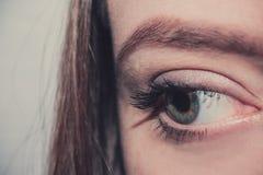 Chiuda su degli occhi femminili che cercano - isolati sopra un fondo bianco Fotografia Stock