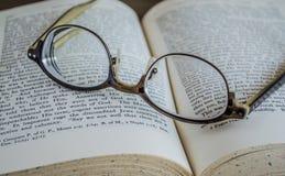 Chiuda su degli occhiali sopra un libro aperto Fotografie Stock