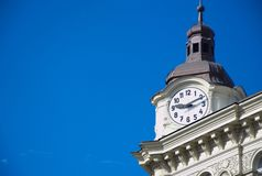 Chiuda su degli orologi sulla costruzione con la torre e sul cielo blu nei precedenti fotografia stock
