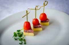Chiuda su degli spiedi con il pomodoro ciliegia, il formaggio ed il salame Immagine Stock