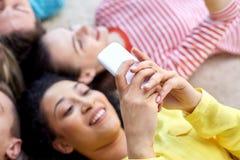 Chiuda su degli studenti o degli amici con gli smartphones Immagine Stock Libera da Diritti