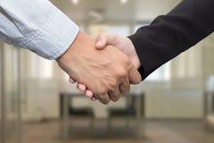 Chiuda su degli uomini d'affari che stringono le mani nella sala riunioni Immagine Stock