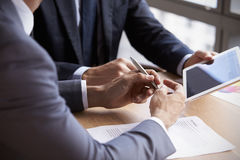 Chiuda su degli uomini d'affari facendo uso della compressa di Digital nella riunione Fotografia Stock Libera da Diritti